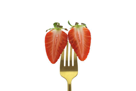 Two halves of a half-cut strawberry pinned on a golden fork isolated on a white background 스톡 콘텐츠