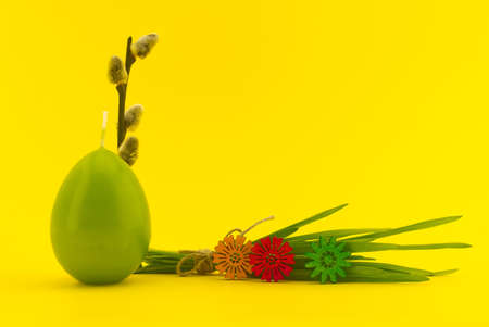 Minimalistic style Easter card with egg shaped candle, willow branch and bundle of wheat seedlings tied with linen twine on yellow background with free copy space