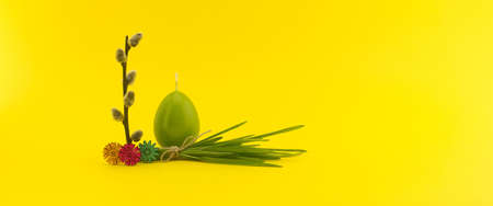 Minimalistic style Easter banner with egg shaped candle, willow branch and bundle of wheat seedlings on yellow background with free copy space for your text 스톡 콘텐츠