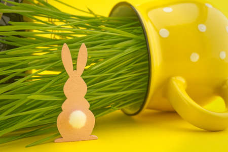 Wheat seedlings growing from a yellow cup and Easter Rabbit figure. Creative Easter holiday background 스톡 콘텐츠