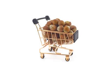 Shopping cart filled with whole ripe hazelnuts isolated on white background 스톡 콘텐츠