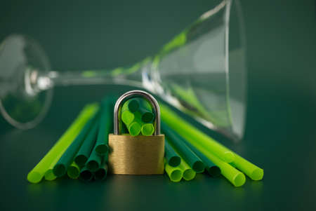 Golden padlock in front of plastic drink straws on a green background. Phase out plastic drinking straws concept 스톡 콘텐츠