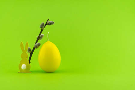 Minimalistic Easter holiday or spring background with Easter Hare figure, pussy willow branch and egg shaped candle over a green background. Copy space for your text 스톡 콘텐츠