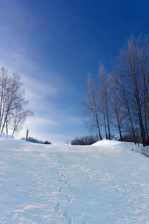 Row of footprints down a mountain slope covered in fresh white snow on a beautiful cold sunny winter day with blue sky looking up from below to trees and the roof of a house on the horizon
