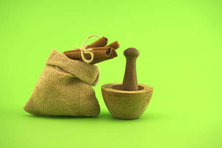 Cinnamon sticks bundle tied with jute string on top of hessian bag and wooden mortar with pestle over green background and free copy space for text 스톡 콘텐츠
