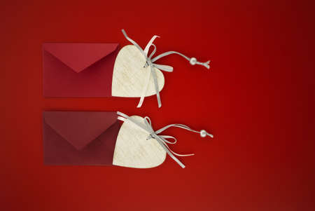 Heart medallions and envelopes on red background with free space for text. Greetings and love letter