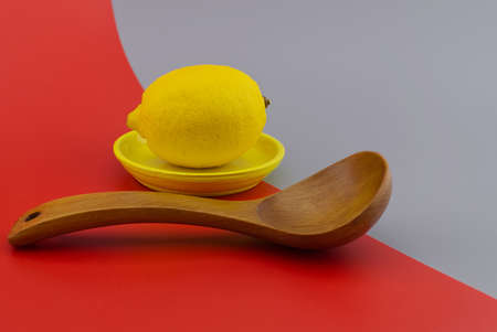 Lemon on a yellow plate next to a wooden spoon on a two tone grey and red background with copy space. Color trends concept
