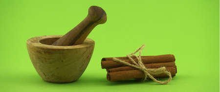 Cinnamon sticks bundle tied with jute string and wooden mortar with pestle on green background and free copy space for text 스톡 콘텐츠