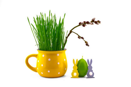 Wheat seedlings growing from yellow cup with pussy willow branch, green egg shaped candle and Easter Rabbit figure isolated on white background