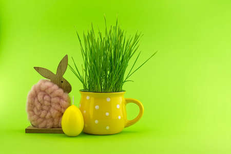 Easter Decoration with wheat seedlings growing from yellow cup, egg shaped candle and Easter Rabbit figure over a green background with free copy space for text 스톡 콘텐츠