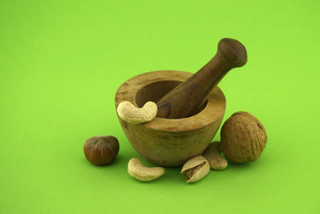 Wooden rustic-style mortar and pestle and various nuts over green background with free space for text. Spices and herb grinder