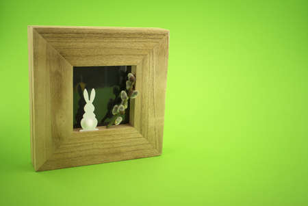 Easter Decoration with photo frame, Easter Rabbit figure and pussy willow branch over a green background. Happy Easter card concept with free copy space for text