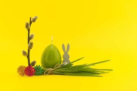 Creative Easter holiday or spring background with egg shaped candle, pussy willow branch and bundle of wheat seedlings tied with linen twine on yellow background with free copy space 스톡 콘텐츠