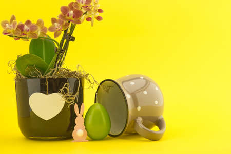 Easter Decoration with flowers, egg shaped candle and Easter Rabbit figure over a yellow background. Happy Easter card concept with free copy space for text