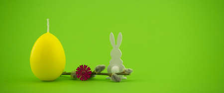 Minimalistic style Easter banner with yellow egg shaped candle, pussy willow branch and Easter Bunny figure over a green background with free copy space for your text