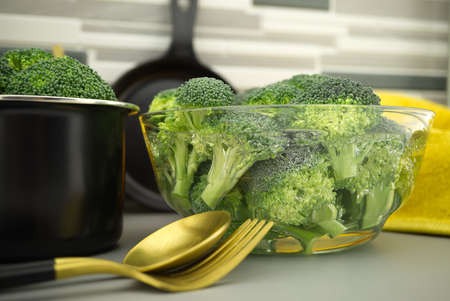 Broccoli preparation for cooking on the kitchen table, broccoli florets soaked in a clear bow 스톡 콘텐츠