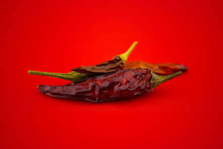 Dried chili peppers on red background. Macro image 스톡 콘텐츠
