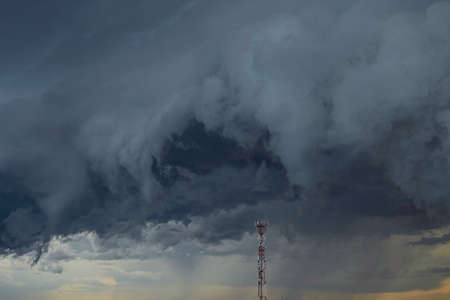 Cell tower on a background of a stormy sky. Light on the horizon