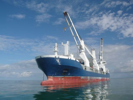 anchored: big cargo ship anchored in the ocean waiting for delivery Stock Photo