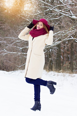 Young, beautiful and stylish red hair girl in coat and hat in the forest. Fashion.
