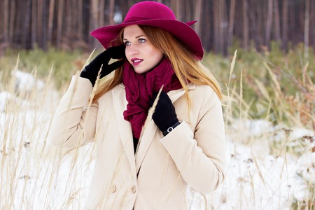 Beautiful, young and stylish girl in coat and hat straightens her hair. Fashion. Stock Photo