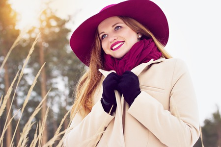 Stylish, young, beautiful and smiling red hair girl in coat and hat in the forest. Fashion.