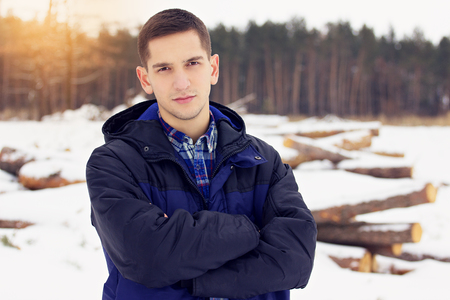 Handsome, stylish and young man in jacket standing in the forest. Early spring, sunny day. Mens fashion.
