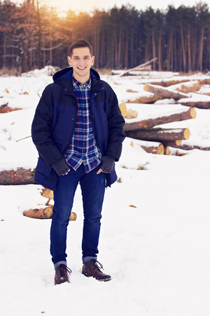 Handsome, stylish and smiling young man in jacket standing in the forest. Early spring, sunny day. Mens fashion. Foto de archivo