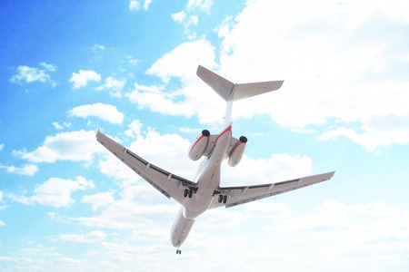 airstrip: Plane flying through clouds in the sky. Jet aircraft in the air. Stock Photo