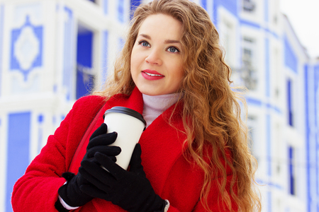 Young, beautiful and stylish blonde hair girl in red coat drinking coffee on the city street. Womens fashion.