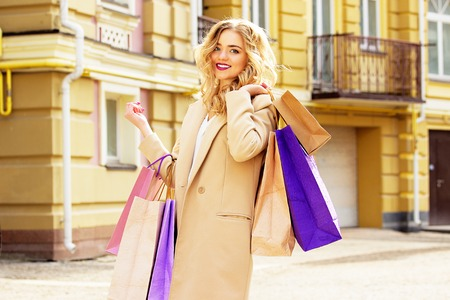 shoppings: Portrait of stylish, beautiful blonde hair smiling girl with shoppings. Happy shopping.
