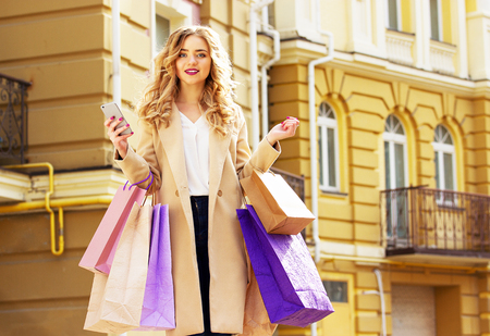shoppings: Stylish, beautiful blonde hair smiling girl with shoppings and phone in her hands. Happy shopping.