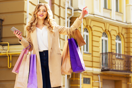 shoppings: Stylish, beautiful blonde hair smiling girl with shoppings calling taxi. Happy shopping.