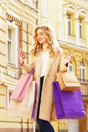 shoppings: Stylish, beautiful blonde hair smiling girl with shoppings using her phone. Happy shopping.