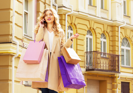 shoppings: Stylish, beautiful blonde hair smiling girl with shoppings talking phone. Happy shopping.