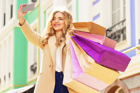 shoppings: Stylish, beautiful blonde hair smiling girl with shoppings taking selfie on her phone. Happy shopping.