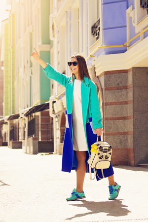 Taxi, I am here. Fashionable, young and beautiful girl in blue coat and sunglasses calling taxi on the city streets.
