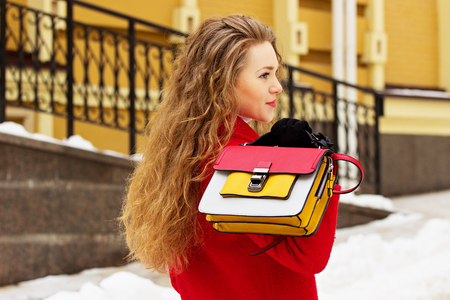 mujeres de espalda: Young, beautiful and stylish blonde hair girl in red coat and keeping handbag on her back. Womens fashion.