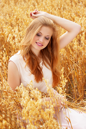Portrait of young and attractive smiling red haired girl dressed in white dress posing in yellow wheat field.