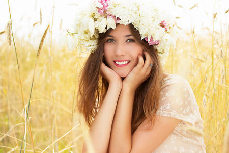 Be happy. Portrait of beautiful smiling woman dressed in white dress is touching her face while sitting on yellow wheat field.