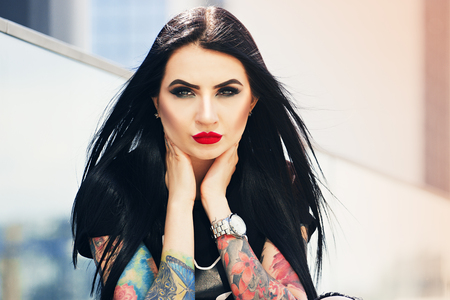 Tattoo fashion. Portrait of stylish tattoed hipster girl in touching her face while standing against urban background.