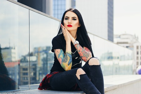 シティ スタイル。都市の背景に座って彼女の顔に触れる魅力的な若い tattoed 内気な少女の肖像画。