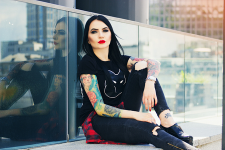 Gorgeous tattoed woman. Portrait of young tattoed hipster girl posing against urban background. Stock Photo
