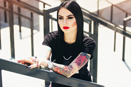 Tattoo fashion. Portrait of fashionable tattoed hipster girl with red lips posing against urban background.