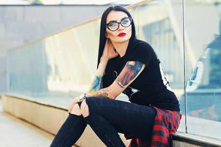 Gothic beauty. Portrait of attractive tattoed hipster girl in glasses posing to camera while sitting against urban background.