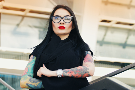 Gothic beauty. Portrait of attractive tattoed hipster girl keeping arms crossed while standing against urban background. Stock Photo