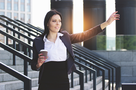Hey, I am here. Portrait of attractive business woman in smart casual wear calling her colleagues while drinking coffee near office building. Stock Photo