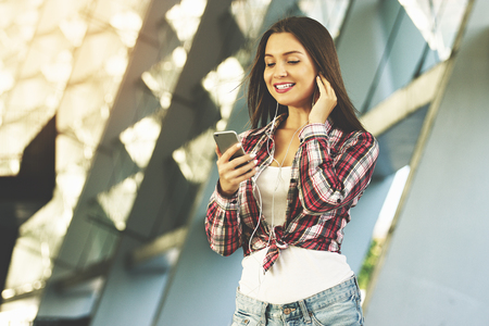Keep in touch. Portrait of stylish beautiful and young woman in hipster wear holding a smart phone in hand and smiling while listening music outdoors.