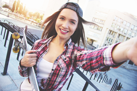 Happy moments must be saved. Cheerful, young and beautiful hipster woman in shirt and cap holding camera and taking selfie while keeping skateboard in another hand.