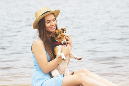 My lovely pet. Portrait of beautiful young woman in dress and hat keeping eyes closed and smiling while holding little pretty dog in her hands.